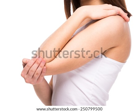 Acute pain in a woman elbow. Female is holding hand to spot of elbow pain indicating location of the pain. Isolation on a white background. - stock photo