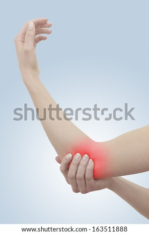 Acute pain in a woman elbow. On light blue background. Color Manipulation image to emphasize the pain. - stock photo