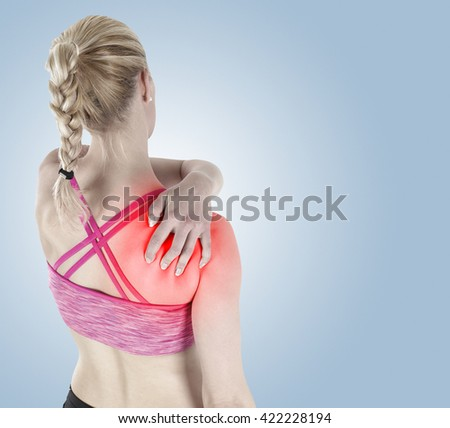 Acute pain in a woman shoulder. Female holding hand to spot of shoulder-aches.  - stock photo