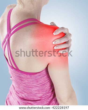 Acute pain in a woman shoulder. Female holding hand to spot of shoulder-aches.