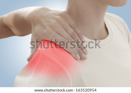 Acute pain in a woman shoulder. Female holding hand to spot of shoulder-aches. Concept photo with Color Enhanced blue skin with read spot indicating location of the pain. On light blue background.