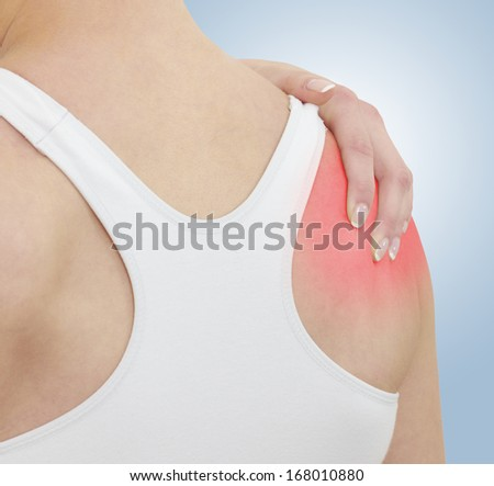 Acute pain in a woman shoulder. Female holding hand to spot of shoulder-aches. Concept photo with Color Enhanced blue skin with read spot indicating location of the pain. - stock photo