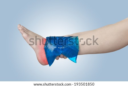Acute pain in ankle. Woman holding hand to spot of ankle-aches. - stock photo