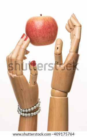 Adam, Eve and the apple. Black background with copy space. Two fingers with painted nails woman touching the fruit. - stock photo