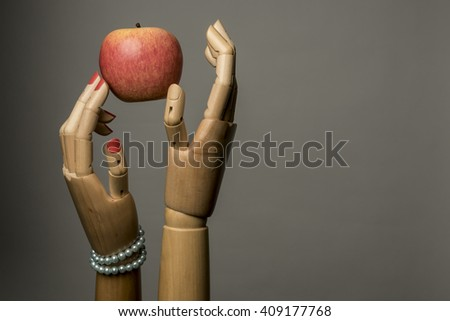 Adam, Eve and the apple. Grey background with copy space.Two fingers of women with painted nails touch the fruit. - stock photo