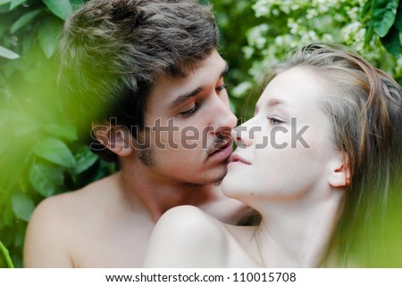 Adam & Eve: Young beautiful happy romantic couple embracing tenderly among green leaves