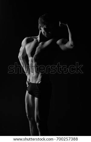 Adam with bare chest. Man with muscular body. Sport and workout. Athletic bodybuilder pose in pants. Gladiator or atlant, black and white