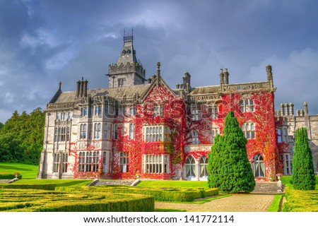 Adare castle in red ivy and gardens, Ireland - stock photo
