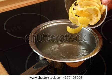 Add lemon peel into saucepan with boiling syrup. Candied Lemon Zest Cooking. Series. - stock photo