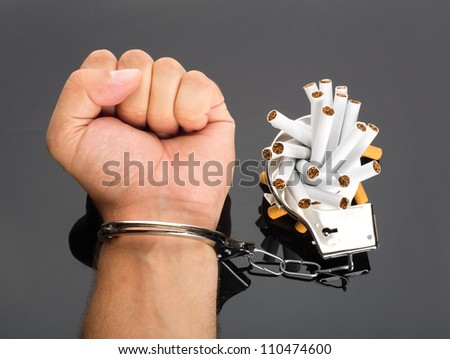 Addict hand locked to cigarettes by handcuffs - stock photo
