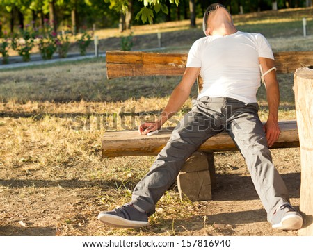Addict man experiencing side effects of injectable drug use, in the park - stock photo