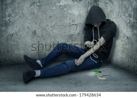 Addict with a syringe using drugs sitting on the floor - stock photo