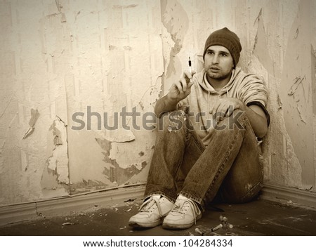 addict with syringes and  with drugs sitting on the floor - stock photo