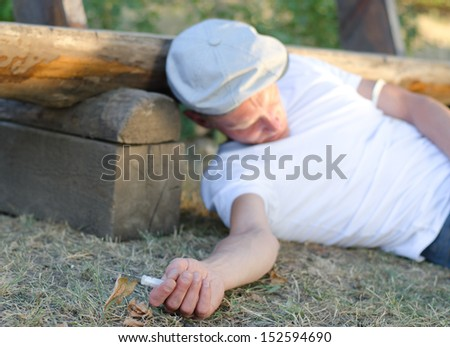 Addicted Caucasian man fainted on the ground after taking an overdose intravenously next to a bench in the park - stock photo