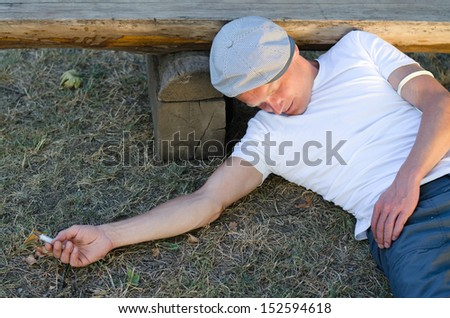 Addicted man fainted on the ground after taking an overdose intravenously next to a bench in the park - stock photo