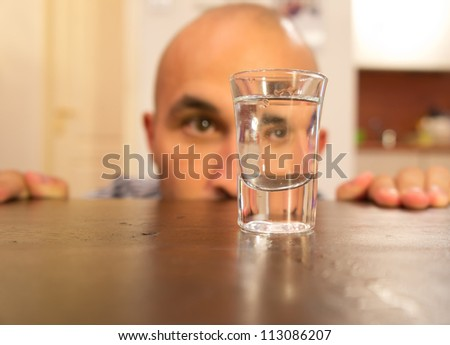 Addicted man looking at a glass filled with alcohol
