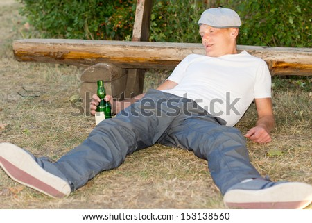 Addicted man lying on the ground experiencing lethargy after excessive drinking - stock photo