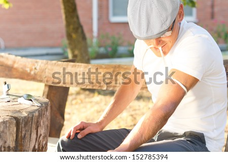 Addicted middle-aged man tying up his left arm in order to take a drug dose through an intravenous injection - stock photo
