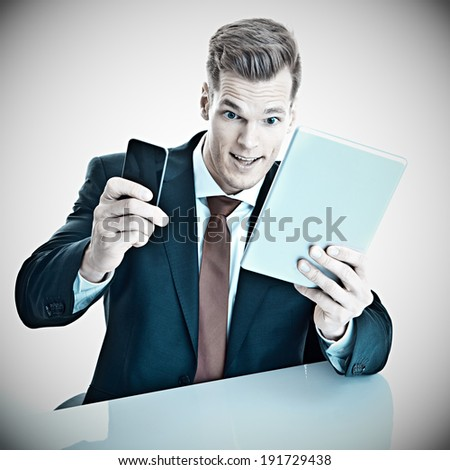 Addicted to his electronic devices - young businessman using tablet and smart phone at the same time and making a crazy facial expression - stock photo