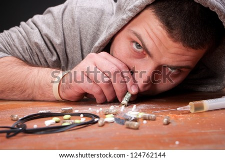 Addicted young man snorting heroin - stock photo