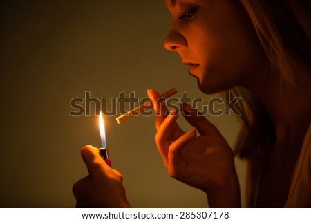 Addiction. Young woman with lighter lighting up cigarette. Addicted girl smoking. Nicotine problem. Studio shot.