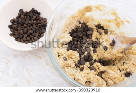 Adding chocolate chips to peanut butter cookie dough in a glass bowl - stock photo