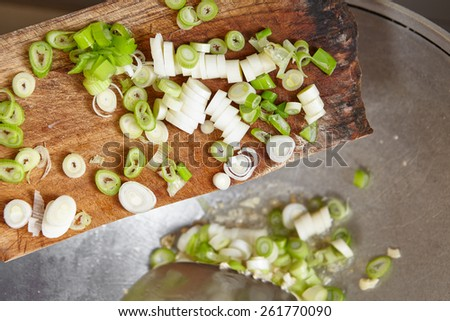 Adding cut leek to the cooking on the wok - stock photo
