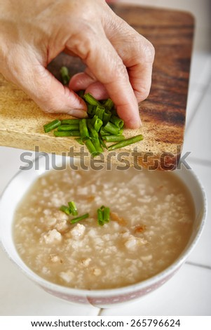 adding cut scallion to  chicken porridge - stock photo