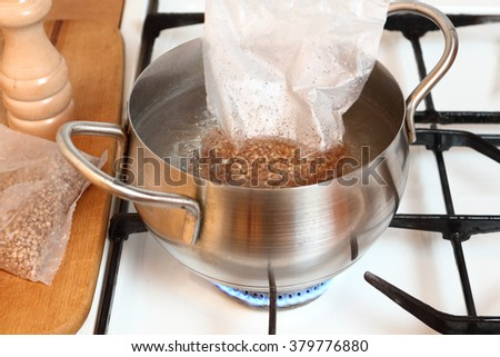 Adding plastic sachets into boiling water. Cooking buckwheat groats on gas stove. - stock photo