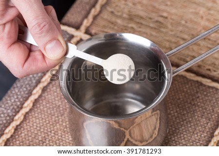 Adding powdered gelatin to water in metal pot. Macro. Photo can be used as a whole background.