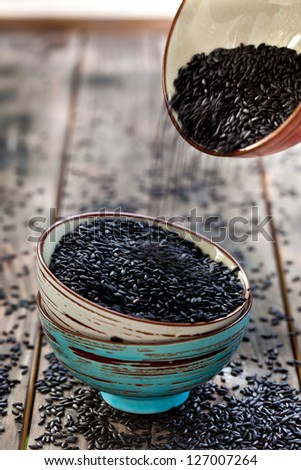 Adding rice to the stack of bowls with black raw rice - stock photo