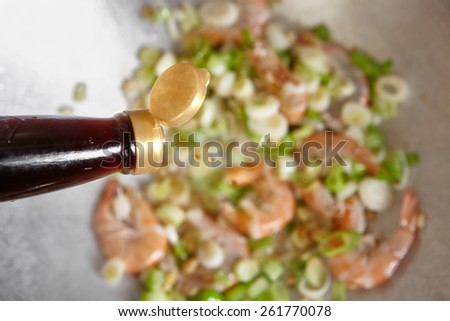 Adding sauce to the cooking ont the wok - stock photo