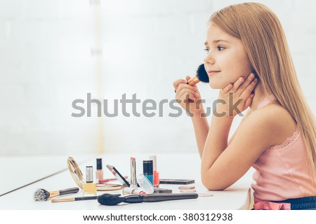 Adding some color to my cheeks. Side view of cheerful little girl applying make-up and looking at her reflection in mirror while sitting at the dressing table - stock photo