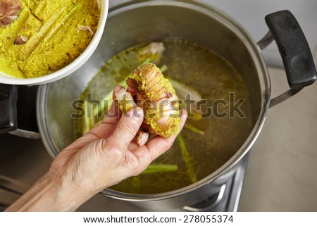 Adding spices and herb to the chicken stock soup - stock photo