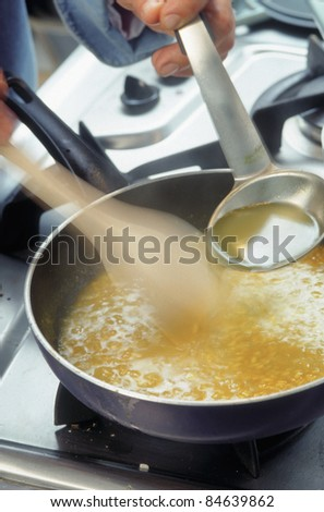 Adding the broth to the preparation - stock photo