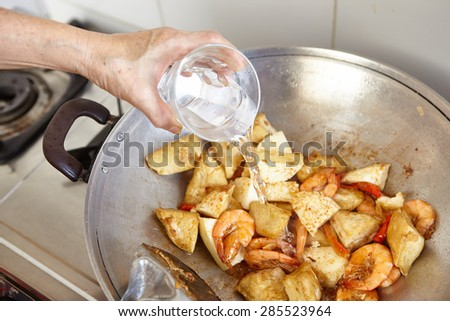 Adding water to the cooking on the wok - stock photo