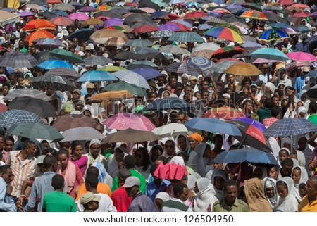 ADDIS ABABA, ETHIOPIA - JANUARY 20: A large crowd with colorful umbrella accompany the Tabot in a colorful procession during Timket celebrations of Epiphany, on January 20, 2013 in Addis Ababa, Ethiopia. - stock photo