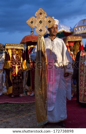 Addis Ababa - Jan 18: A priest carries a large cross in front of priests carrying Tabots, a model of the Arc of Covenant, during Timket celebrations of Epiphany, on January 18, 2014 in Addis Ababa. - stock photo