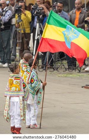 Addis Ababa - May 5: A young boy dressed in colourful traditional outfit holds the Ethiopian flag at the 74th anniversary of Patriots' Victory day on May 5, 2015 in Addis Ababa, Ethiopia. - stock photo