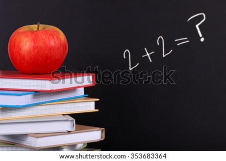 Addition equation written on a blackboard with books and apple in front - stock photo