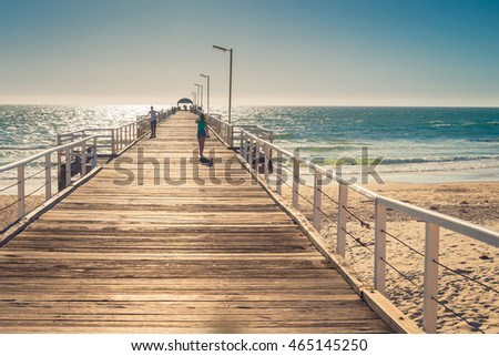 Adelaide, Australia - February 7, 2016: Unrecognized barefoot woman walking along the  Henley Beach Jetty on a warm sunny day. Color-toning applied