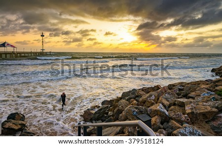 Adelaide, Australia - July 11, 2015: An unknown surfer coming out from the water after riding the waves at sunset near Brighton Beach, South Australia