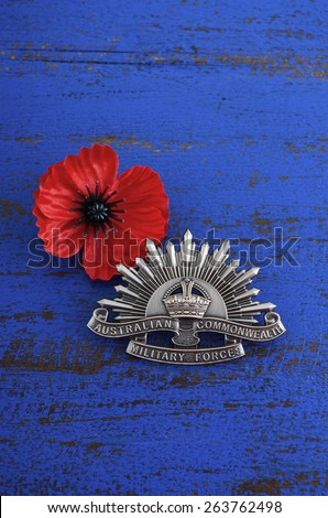 ADELAIDE, AUSTRALIA - MARCH 18, 2015: Australian Anzac WWI rising star hat badge with red Remembrance poppy on dark blue wood background. - stock photo