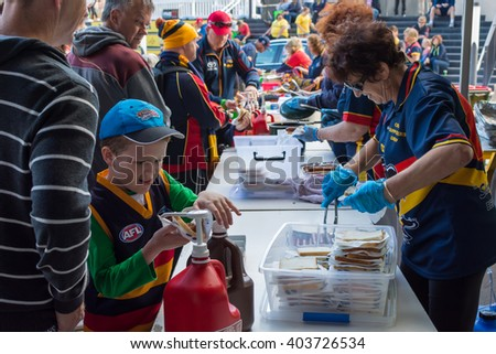 ADELAIDE, AUSTRALIA - MARCH 18, 2016: Crows supporters eat hot dog during season opening.  - stock photo