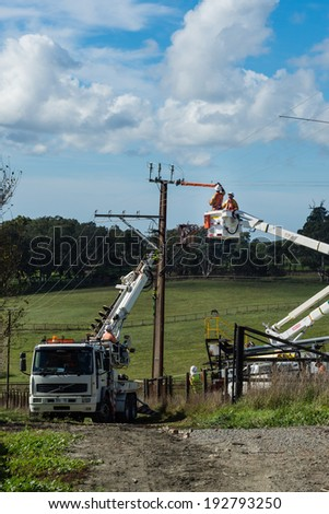 ADELAIDE, SA, AUSTRALIA - MAY 12 2014: image of Power Company employees fixing power transformer, on a rural property. Home owners must by law grant access to power companies onto their land. - stock photo