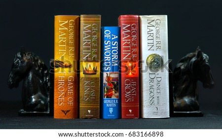 ADELAIDE, SOUTH AUSTRALIA - JULY 12, 2017: Popular fantasy hardcover books, A Song of Ice and Fire, by George R R Martin, between horse head bookends.