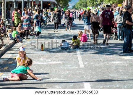 Adelaide, South Australia - November 14, 2015: Kids drawing with chalk on the street during Credit Union Christmas Pageant 2015