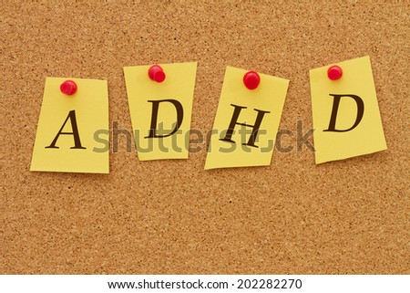 ADHD Notice, Four yellow notes on a cork board with the word ADHD - stock photo