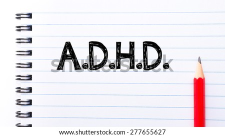 ADHD Text written on notebook page, red pencil on the right. Concept image