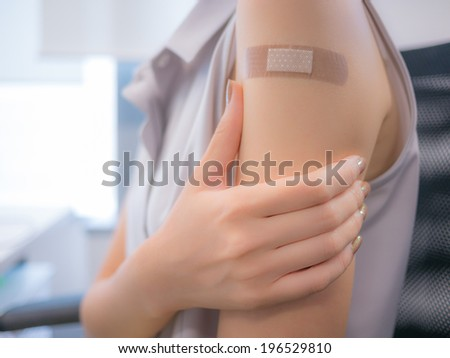 Adhesive bandage on a female arm after vaccination - stock photo